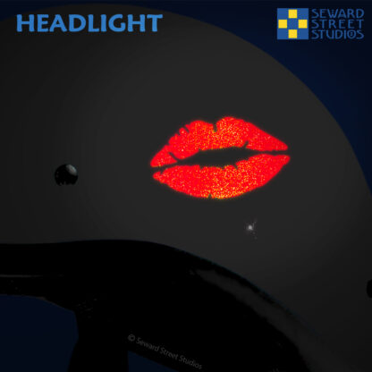 992 Red Hyper Reflective Lips Decal by Seward Street Studios. Shown on a white helmet, at night, demonstrating reflective glow under headlights.