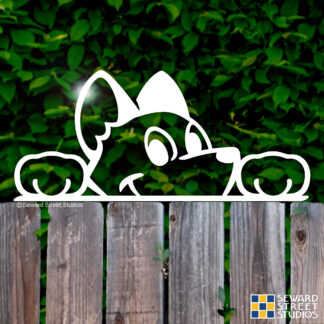 Seward Street Studios Peekaboo Dog Vinyl Decal. Shown on a fence background