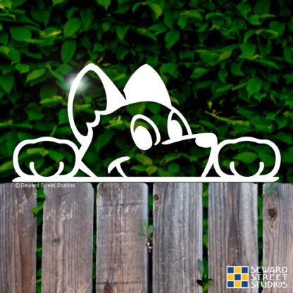 Seward Street Studios Peekaboo Dog Vinyl Decal. Shown on a fence background