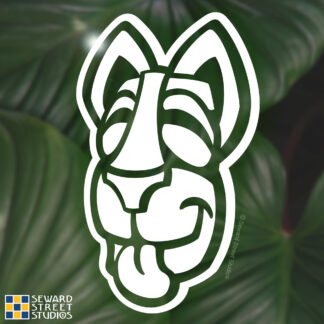 Seward Street Studios Tiki Dog Head Vinyl Decal. Shown on a leaves background