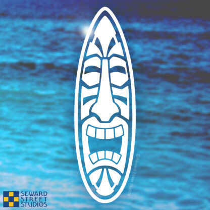 Seward Street Studios Surfboard Tiki Head Vinyl Decal. Shown on a beach background