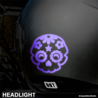 986 Seward Street Studios sugar skull reflective decal shown in purple on a silver helmet at night under headlights