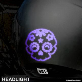 986 Seward Street Studios sugar skull reflective decal shown in purple on a silver helmet at night under headlights