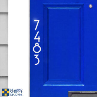 1231 Seward Street Studios Vertical Reflective Address Numbers, shown in white vinyl, in daylight on a blue door