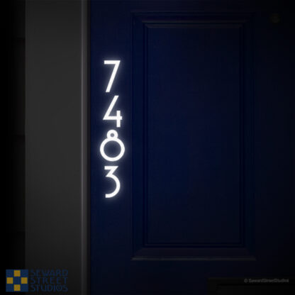 1231 Seward Street Studios Vertical Reflective Address Numbers, shown in white vinyl, at night on a blue door