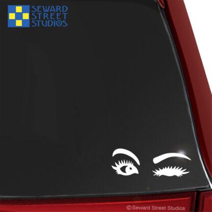1198 Seward Street Studios Winking Eyes decal shown on a red car