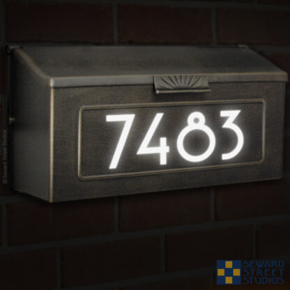 1246 Seward Street Studios Reflective Address Numbers, shown in white vinyl, at night on a wall mounted mailbox