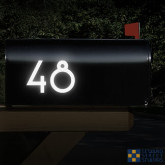 1250 Seward Street Studios Address Numbers Decal, shown in white reflective vinyl, on a black mailbox at night