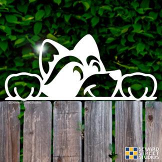 1198 Seward Street Studios Peekaboo raccoon vinyl decal shown on a fence background