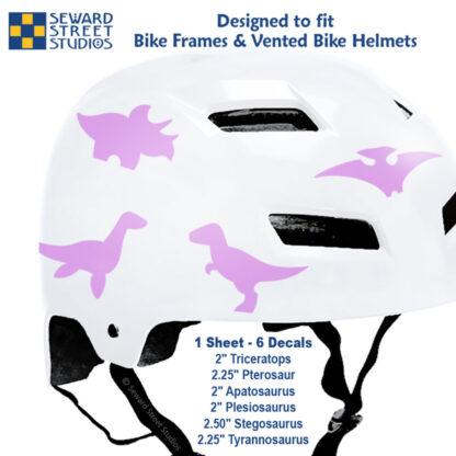 886 Seward Street Studios pink dinosaur decal set shown on a white bike helmet with sizes